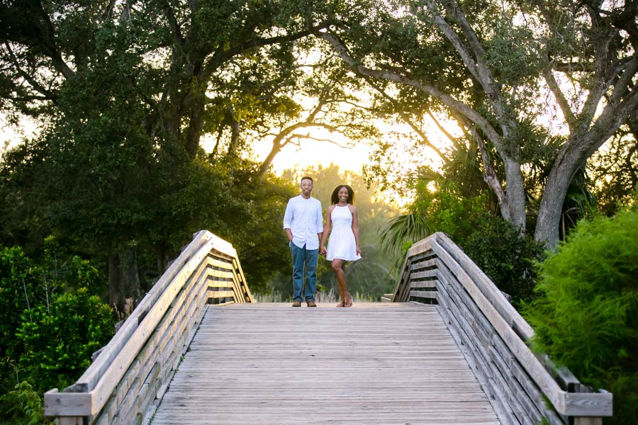 black couple hold hands on wooden bridge | engagement photography tree tops park