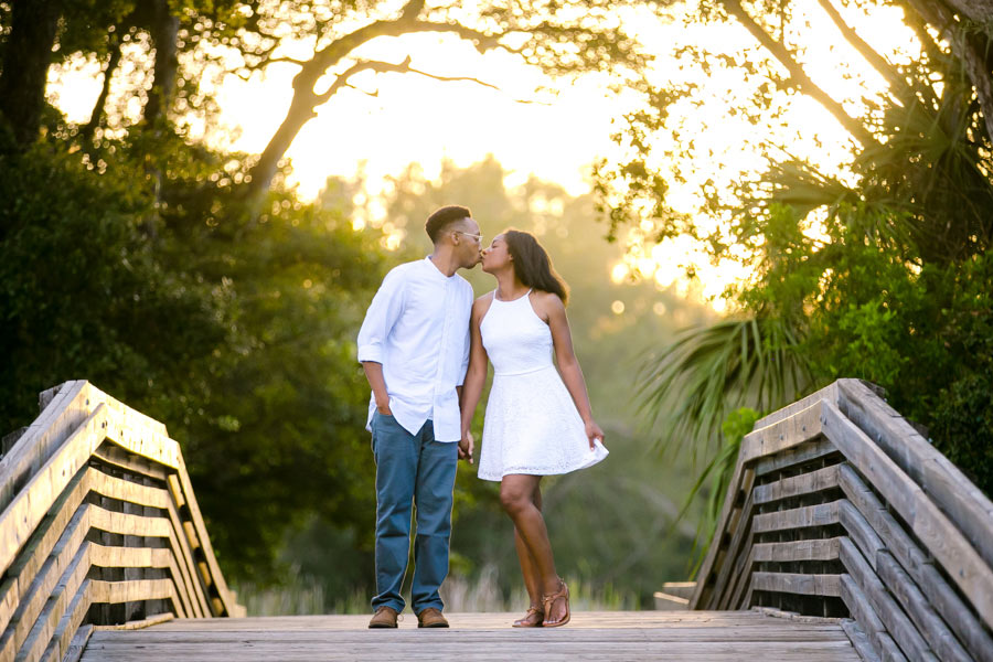 kissing black couple on wooden bridge | tree tops park engagement photoshoot | fort lauderdale engagement photographer