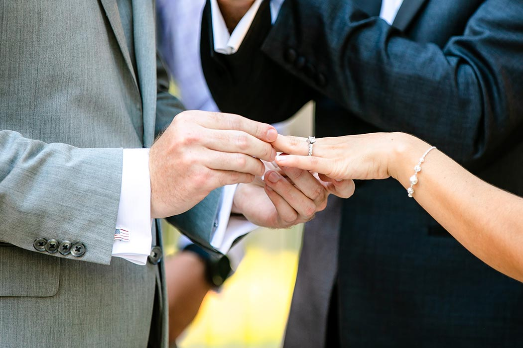 photograph of bride and groom exchanging diamond wedding ring | close up photograph of wedding ring exchange