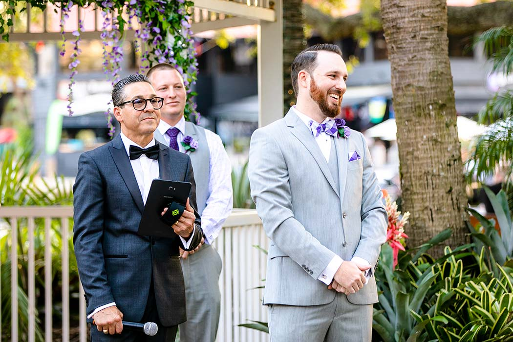 groom in grey suit with purple and white bow tie | groom at alter waiting for bride