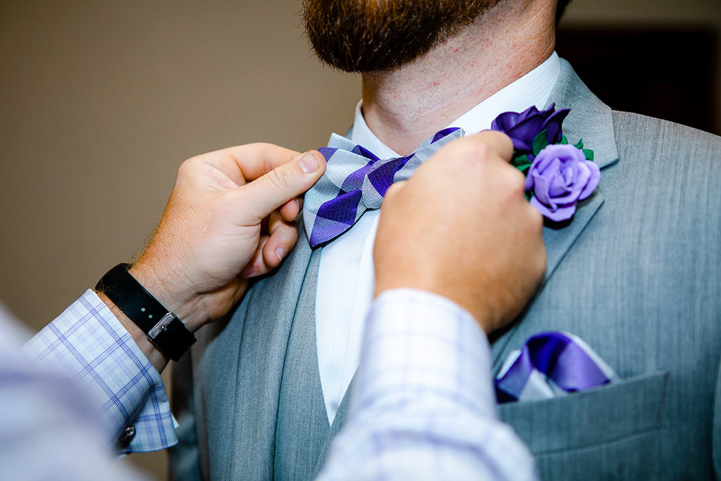 best man adjusts purple and white groom bow tie | fort lauderdale historical society wedding