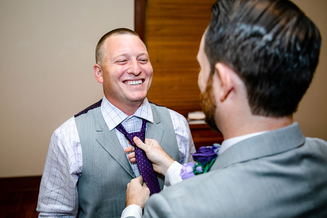 best man helps groom get ready at fort lauderdale historical society | groom wearing purple and white bow tie and accessories