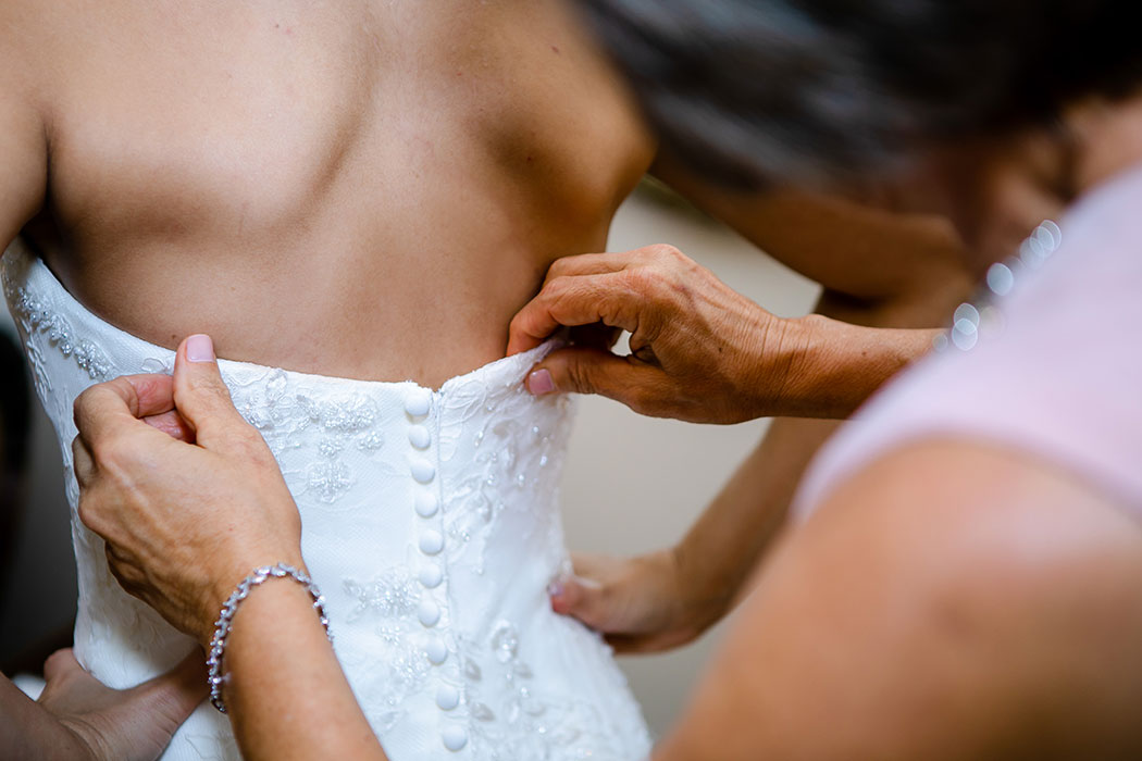 photograph of brides mother fastening wedding dress at the back before her ceremony