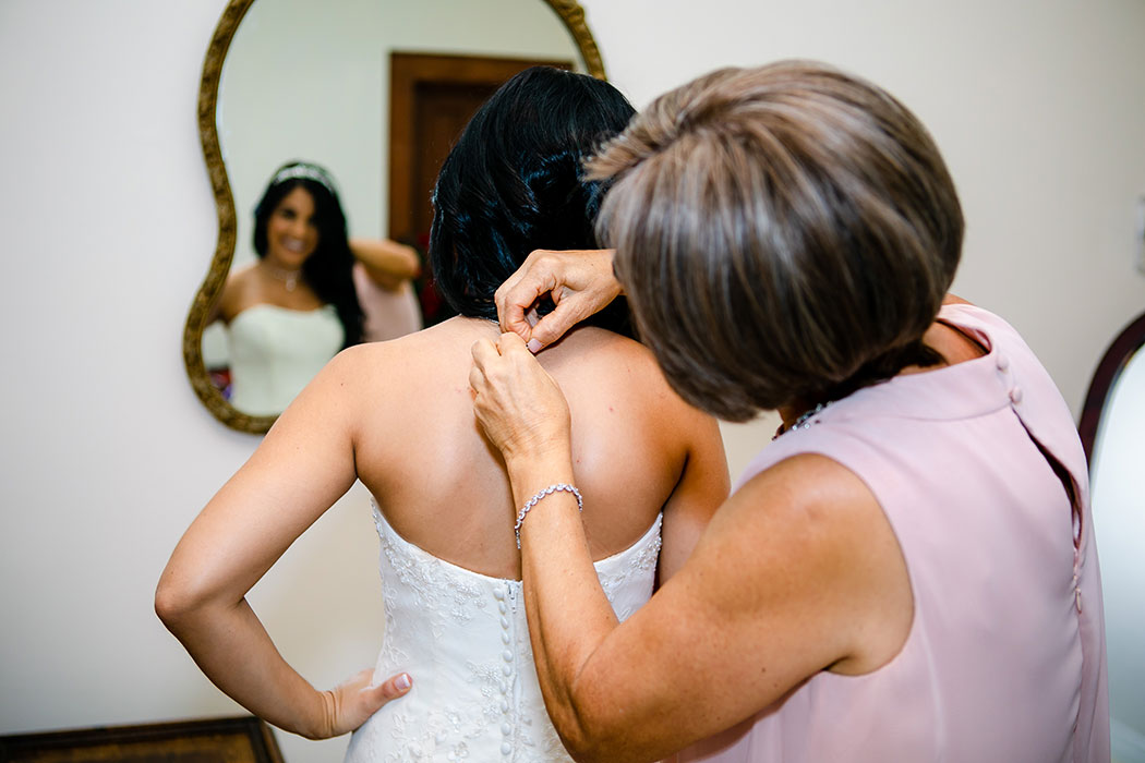 brides mother helps her get ready before her wedding day