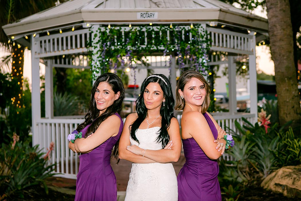 unique photo of bride and bridesmaids | white bridal dress with purple bridesmaids dresses
