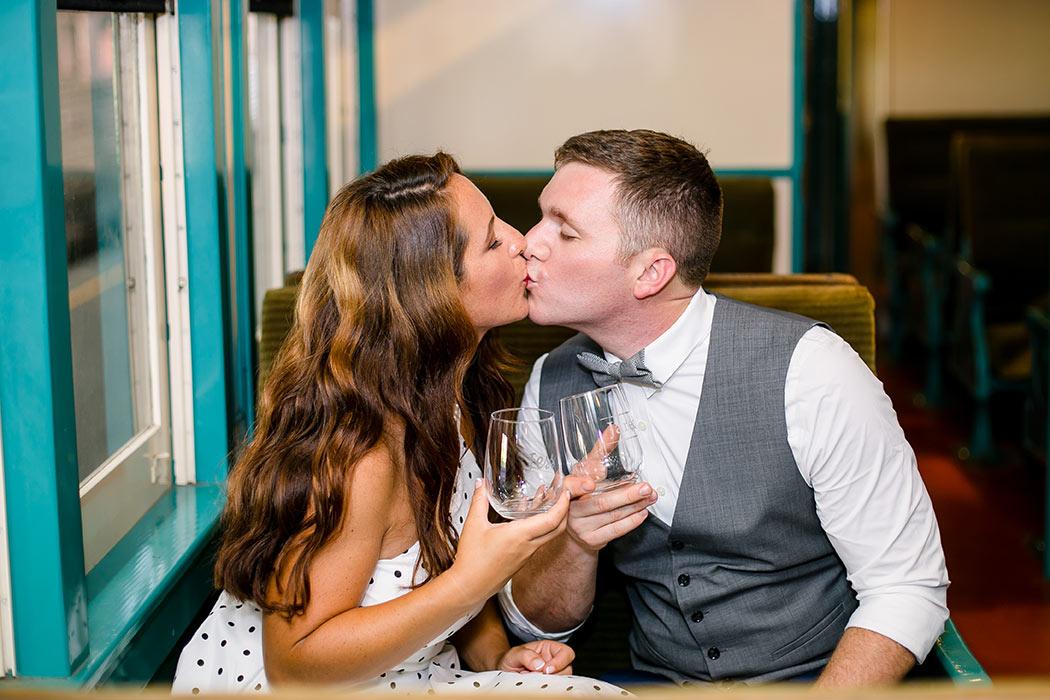 engaged couple kiss on train | vintage engagement themed photoshoot on train