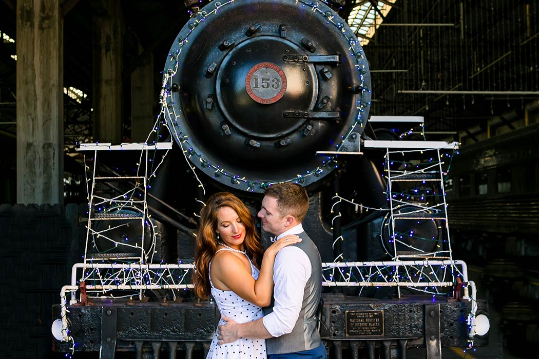 engaged couple posing in front of locomotive | vintage engagement session south florida | engagement session with trains miami