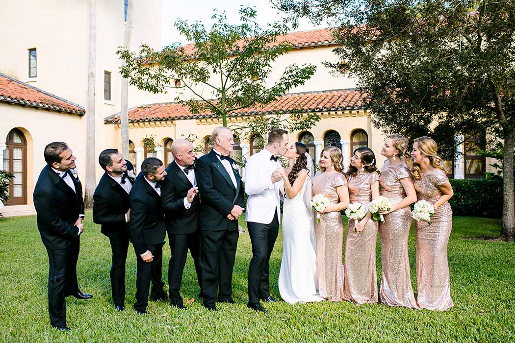 bride and groom kiss with bridal party | unique bridal party poses | gold sequined bridesmaid dress