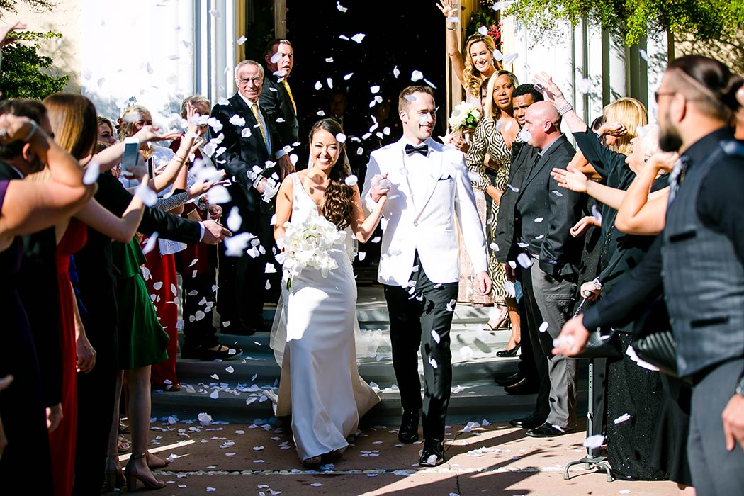 bride and groom exit from church with white petals | miami church wedding