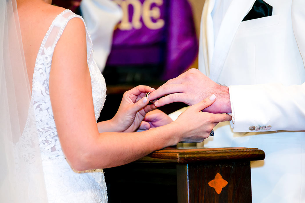 bride puts on grooms ring during miami church wedding | south florida wedding photographer