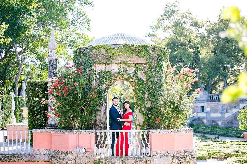 gorgeous couple pose in long red dress and navy suit for engagement pictures at vizcaya | vizcaya photoshoot