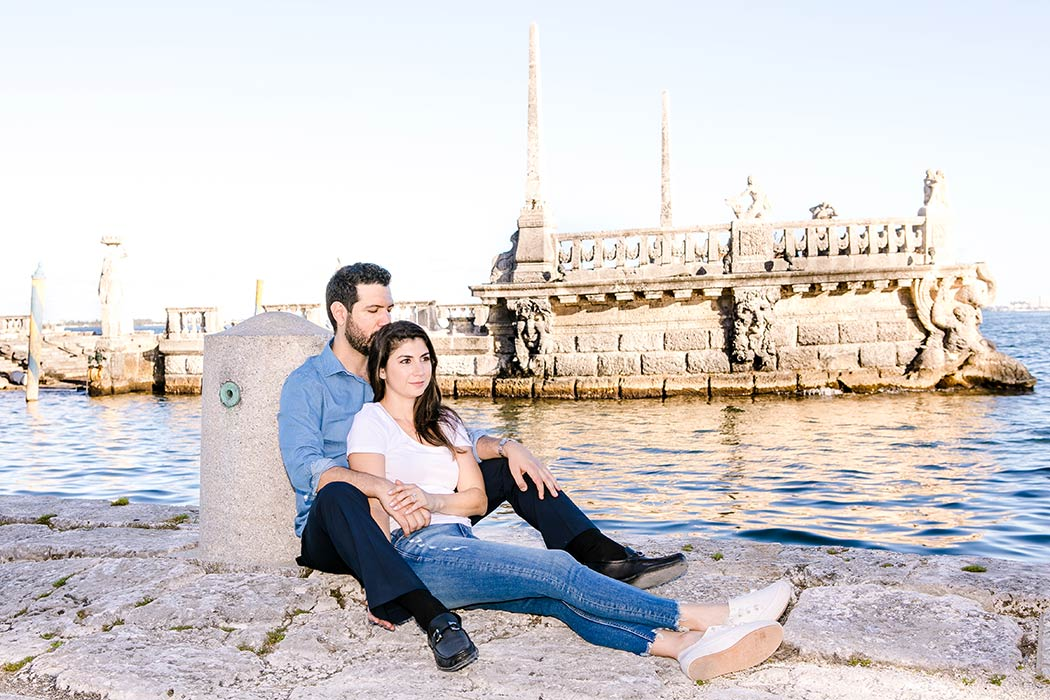 couple pose for engagement photoshoot near water at vizcaya | vizcaya barge photoshoot