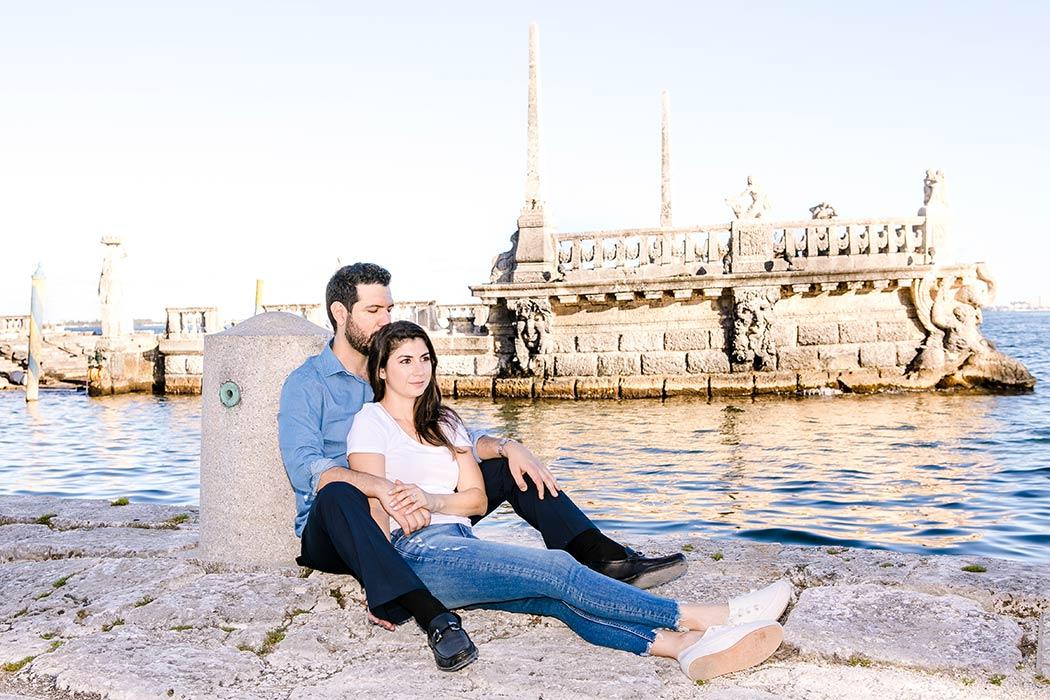 couple pose for engagement photoshoot near water at vizcaya | vizcaya barge photoshoot