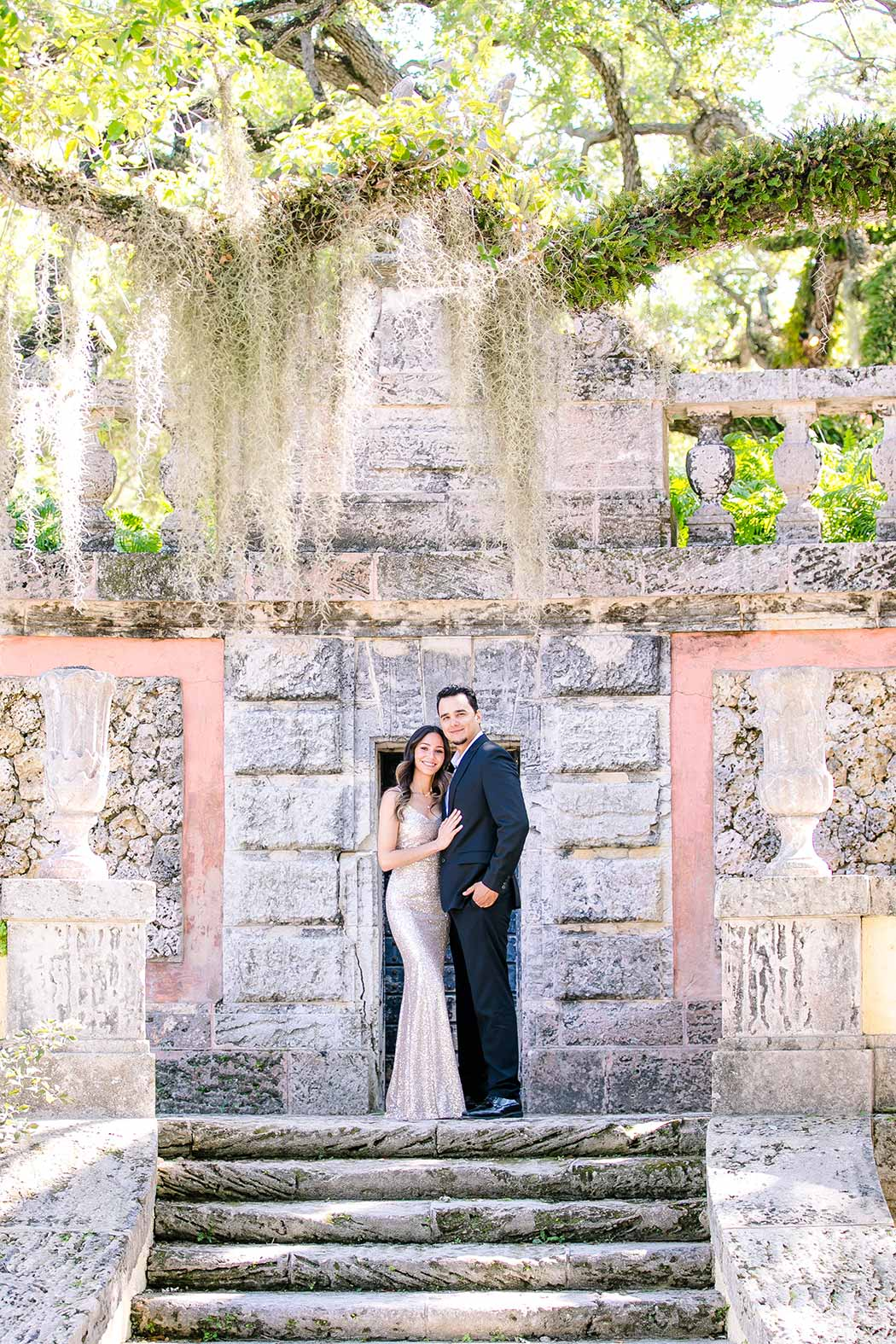 couple pose for engagement photoshoot at vizcaya museum miami | long red dress for engagement