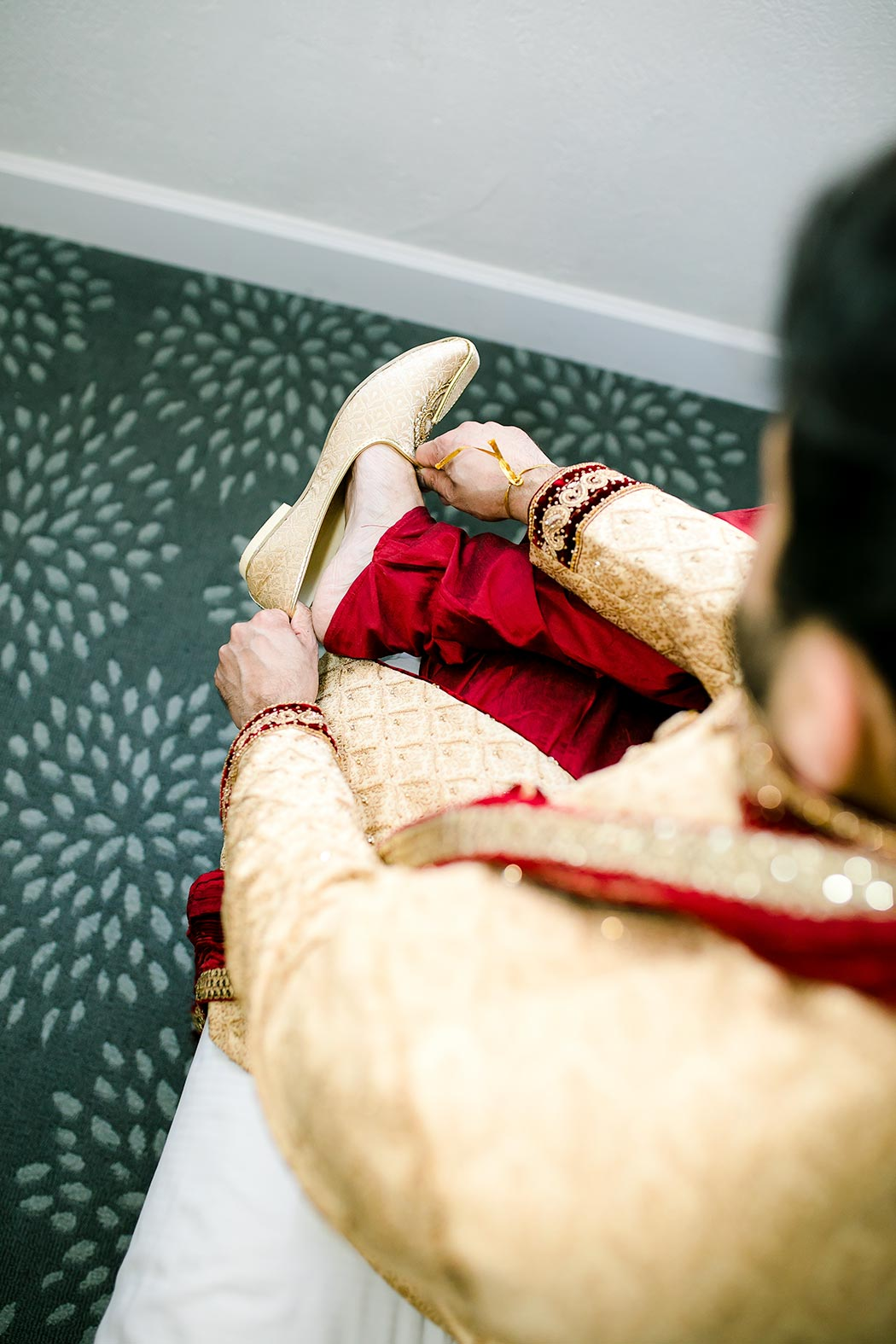indian groom puts on shoes | groom wedding detail photography