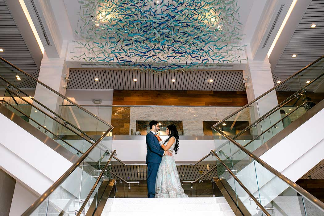 bride and groom pose on stairs of hotel