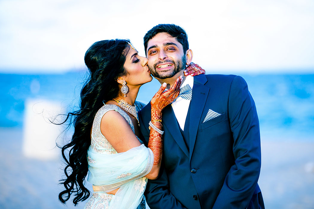 indian bride kisses groom on cheek | indian wedding on beach in fort lauderdale