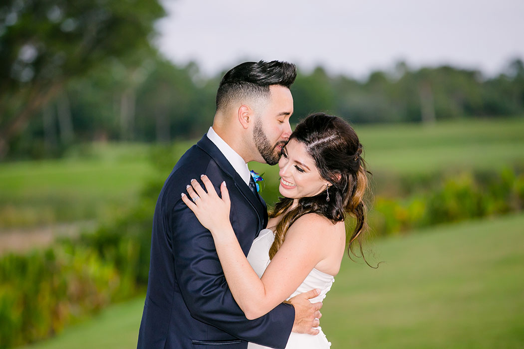 groom kisses bride on cheek | bride and groom on golf course | fort lauderdale wedding photographer