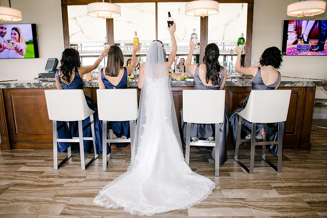 bride and her bridesmaids fun bar shot raising glasses