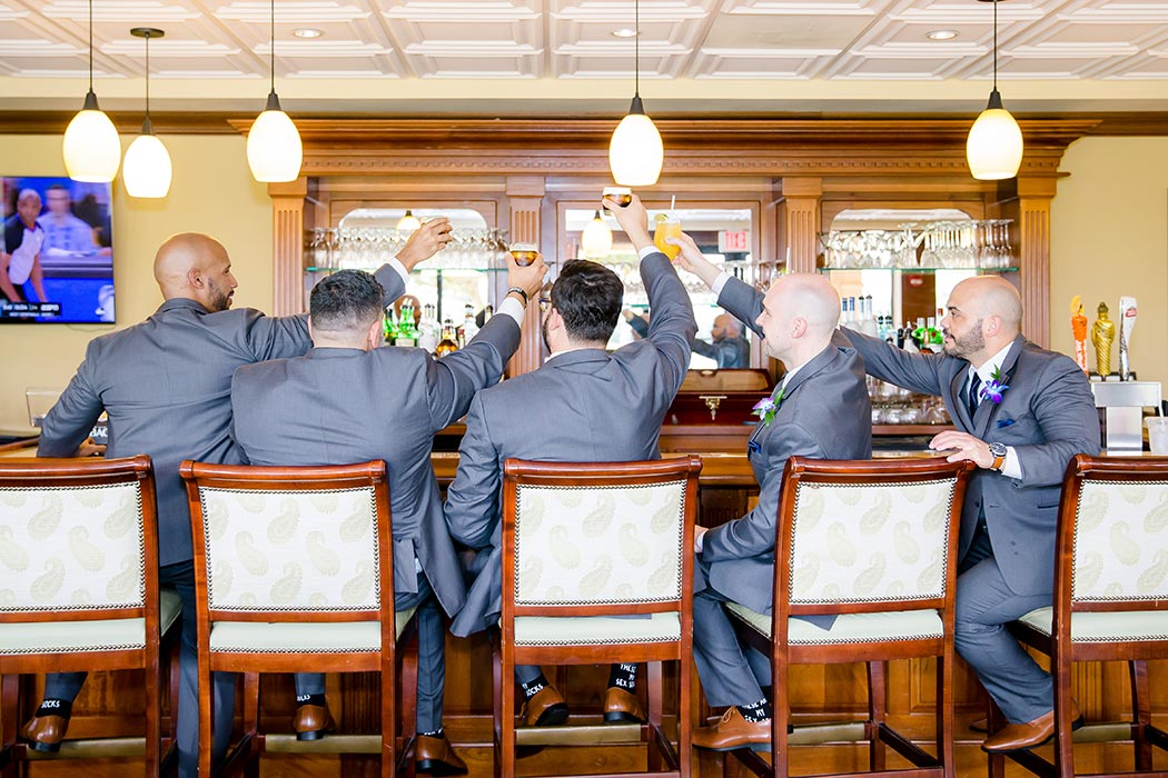 fun photograph with groom and groomsmen at bar | groom and groomsmen raising drink glasses at bar