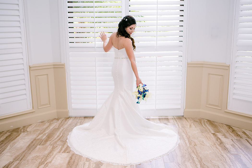 stunning image of bride at window in wedding dress at breakers west country club | photograph of bride in wedding dress at window