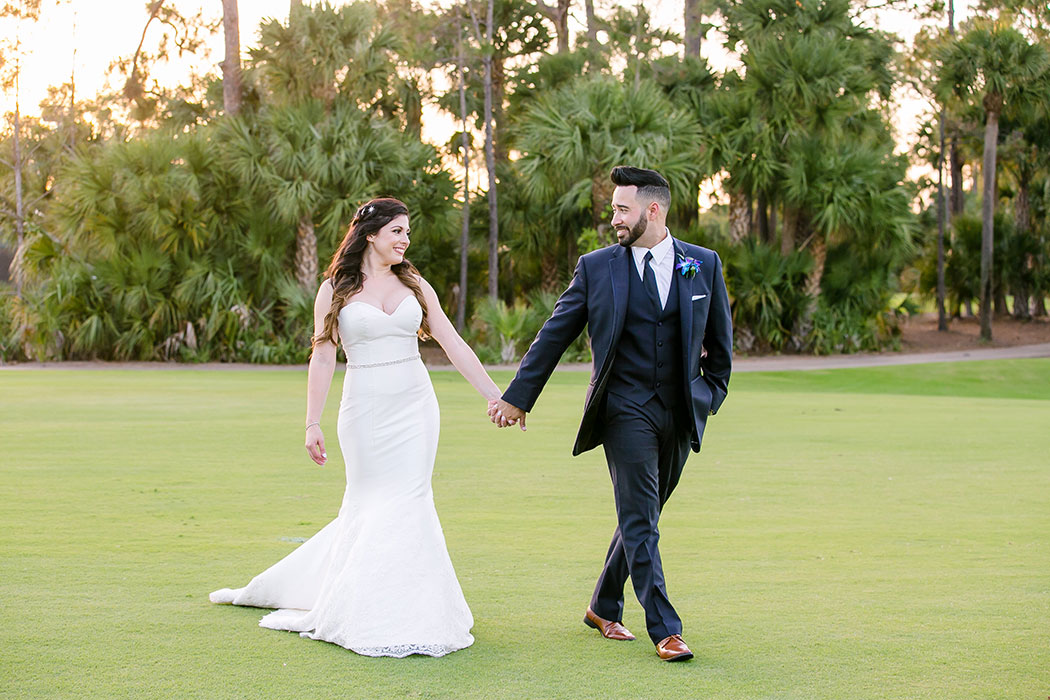 bride and groom holding hands walking across golf course | breakers west country club wedding | wedding in fort lauderdale