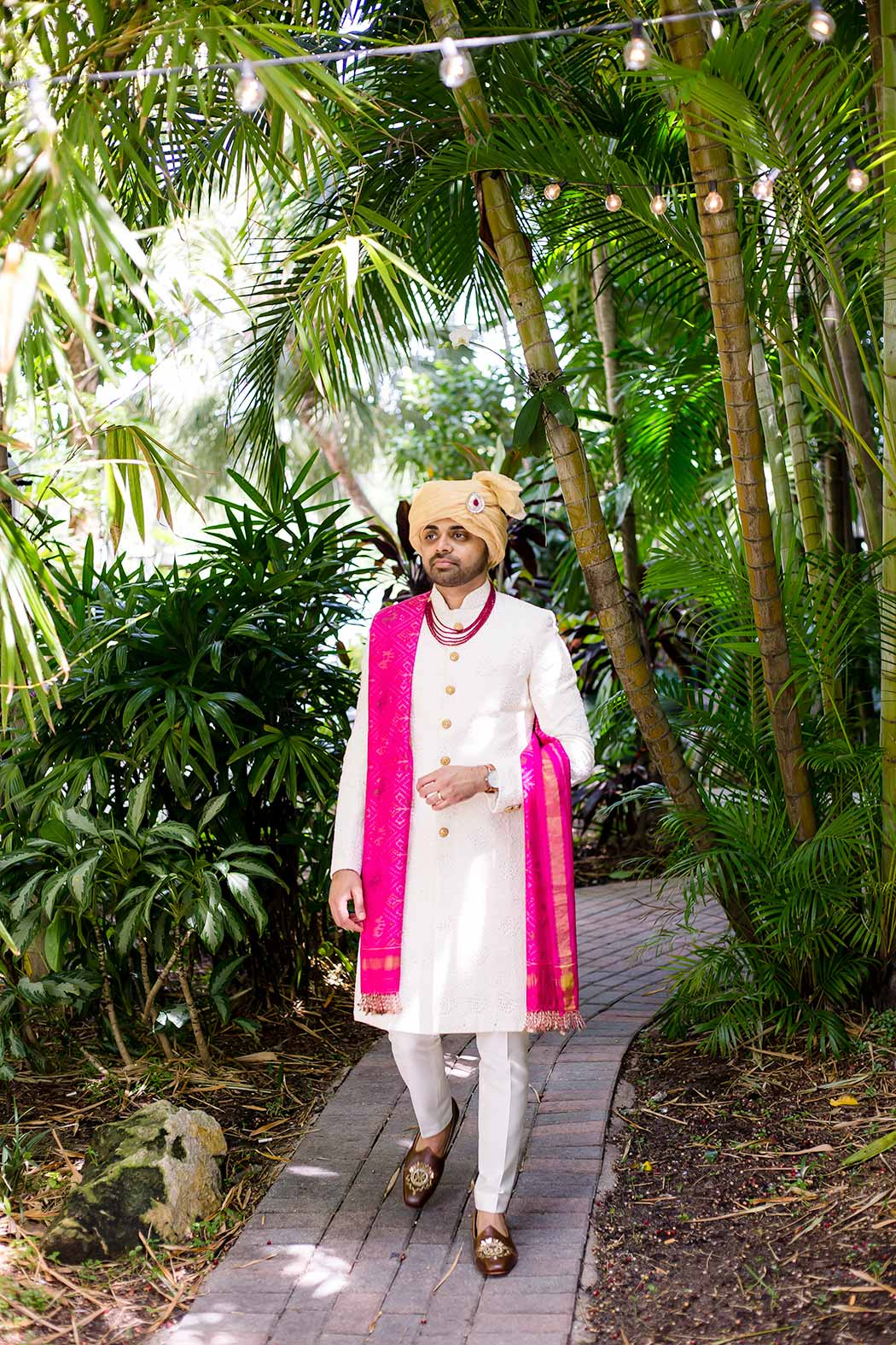 south indian groom prepares for wedding in fort lauderdale | indian groom wearing white suit with pink wrap | gold indian wedding turban | indian groom photograph