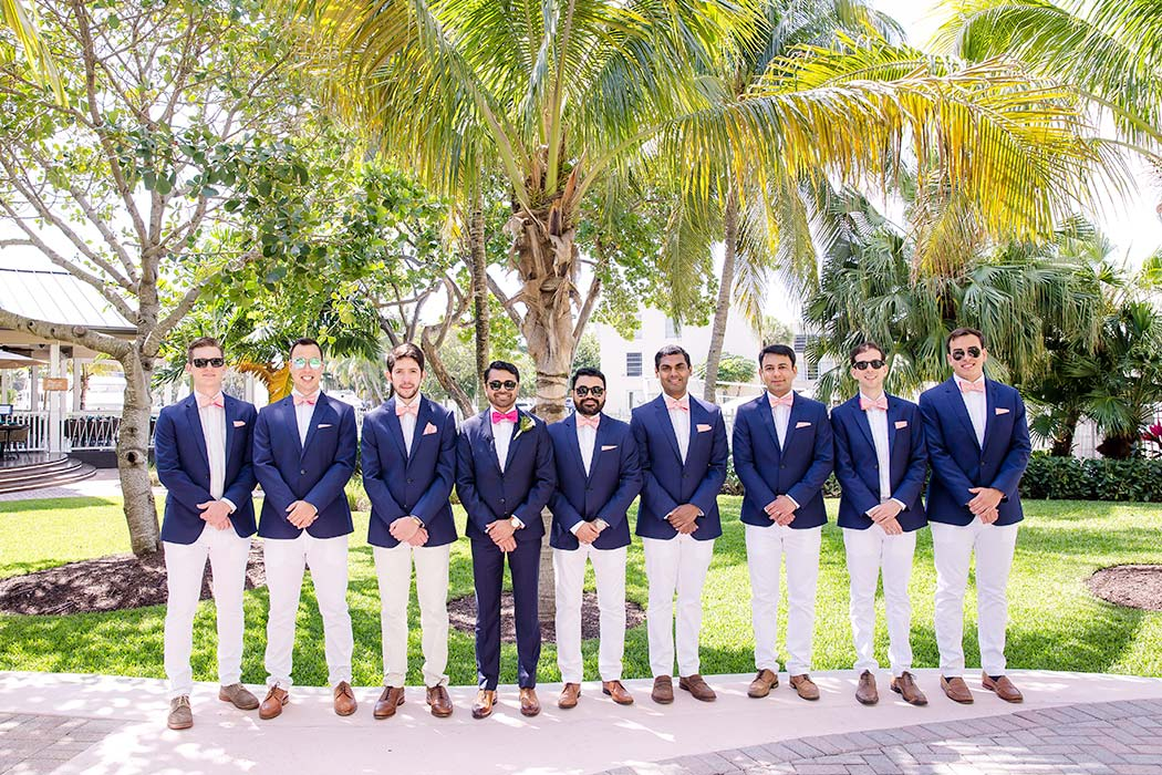indian groom in navy suit and pink bow tie | unique groomsmen pose | indian groom and his groomsmen photograph