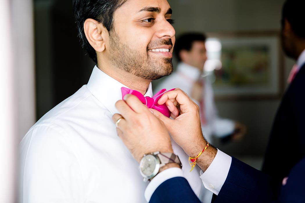 indian groom getting ready in fort lauderdale | hindu wedding fort laudedale | groom in pink bow tie | best man helping groom getting ready | pink wedding bow tie