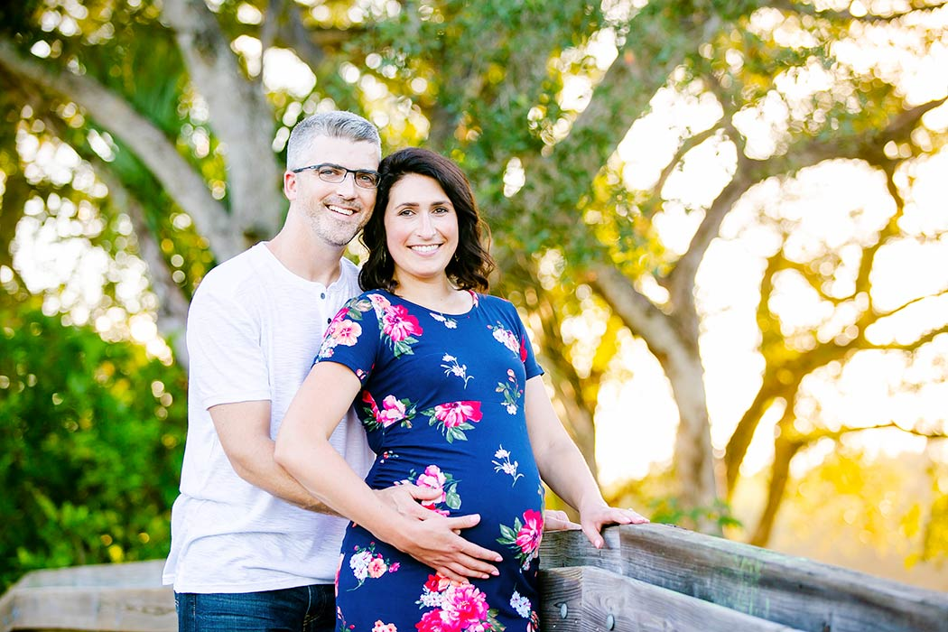 husband and wife maternity pose idea | pose for maternity photography with two people | tree tops park maternity photography | park maternity photoshoot with blue floral maternity dress