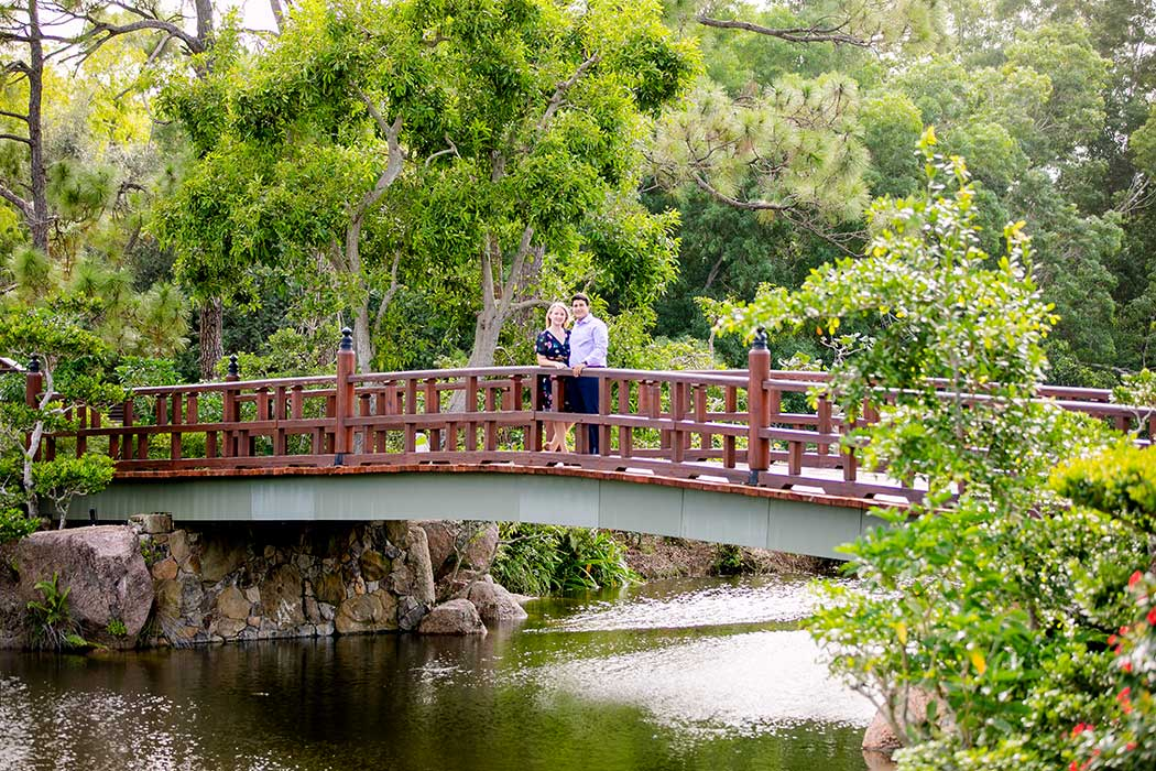 couple stand on bridge in morikami japanese gardens for engagement photoshoot | engaged couple on bridge in morikami | engagement photographer fort lauderdale