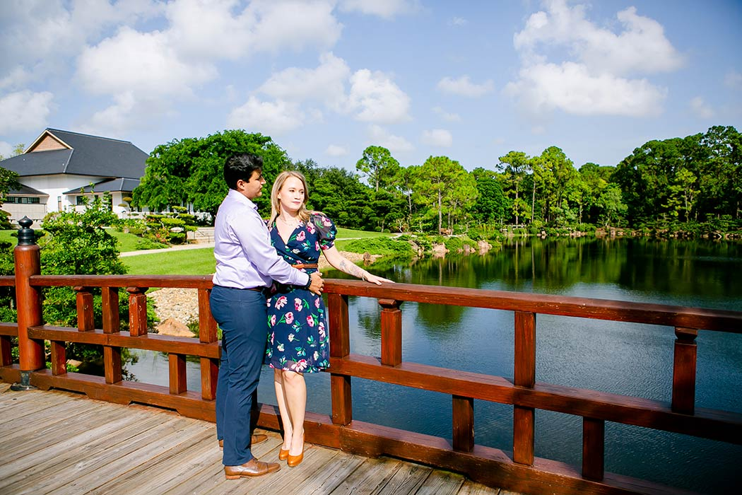 couple pose on bridge at morikami for engagement photo | engagement photography session in morikami museum | engagement session in south florida | engagement photographer south floridark