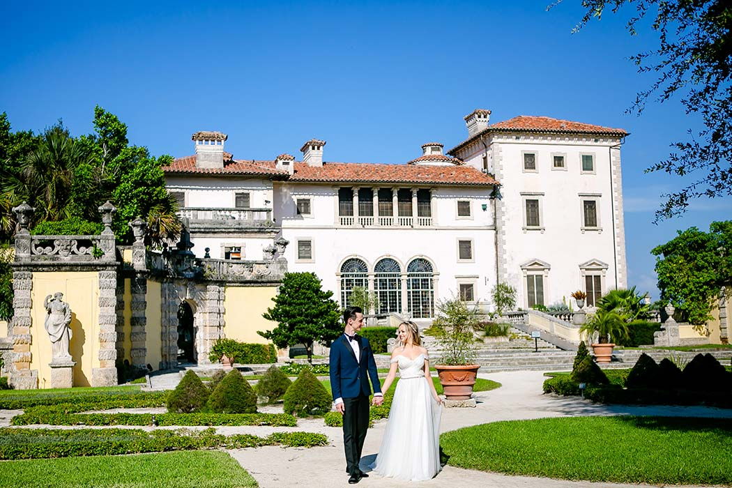 engagement photography at vizcaya | couple walk hand in hand with vizcaya at background | beautiful vizcaya photoshoot