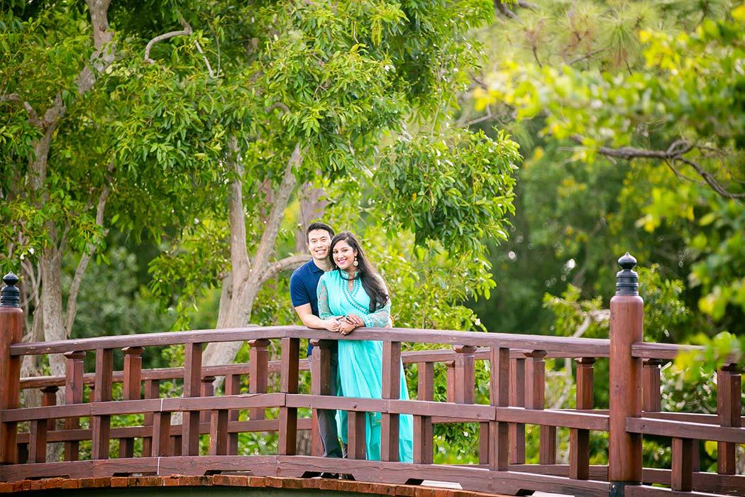 indian couple pose on bridge for engagement photos at morikami | morikami engagement