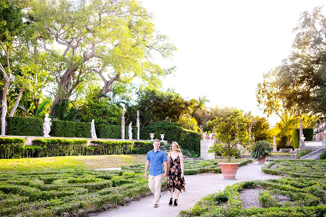engaged couple walking through vizcaya gardens during photoshoot