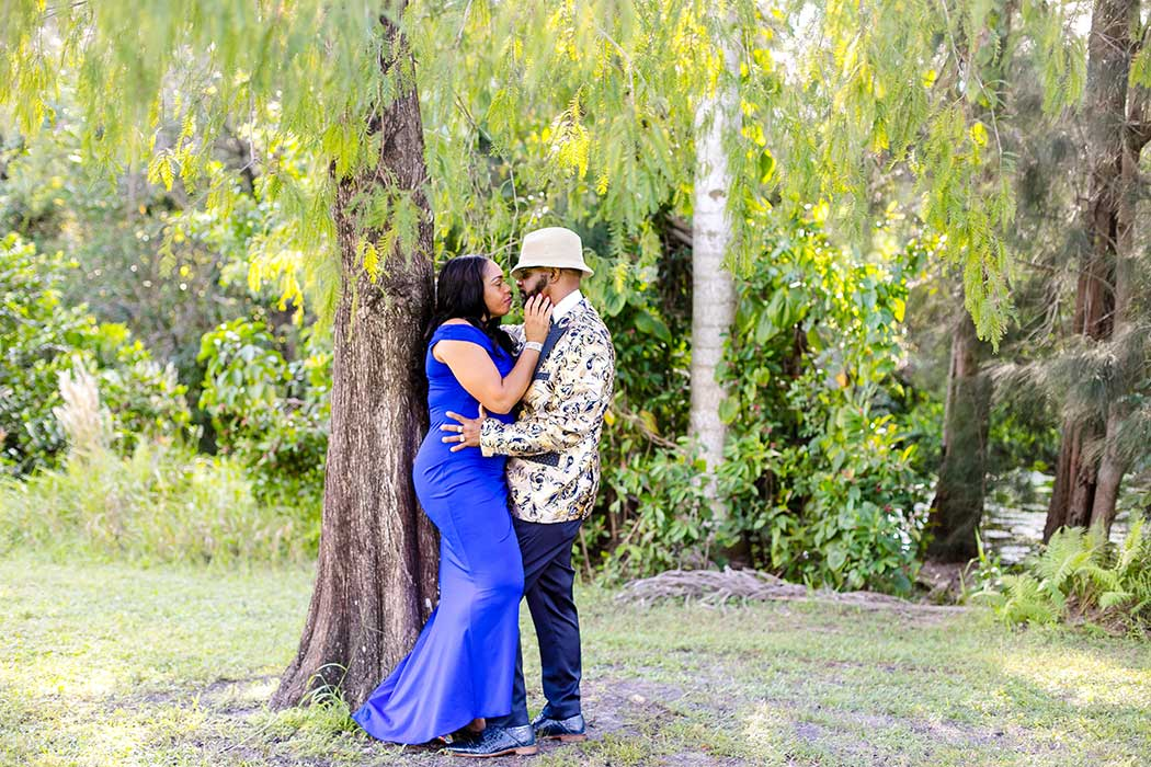 unique photograph of engaged couple standing in front of large tree | tree tops park engagement photoshoot fort lauderdale | fort lauderdale engagement photographer