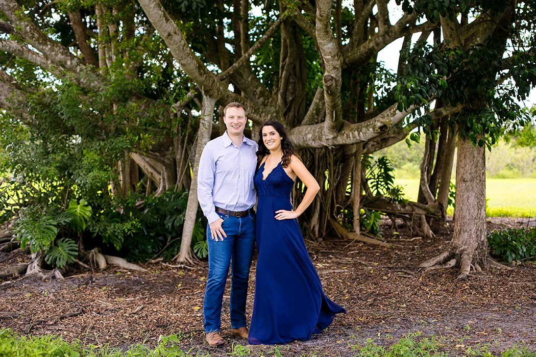 couple pose for robbins park photos | engagement photoshoot robbins preserve park in davie | formal attire for photography | floor length navy blue engagement dress
