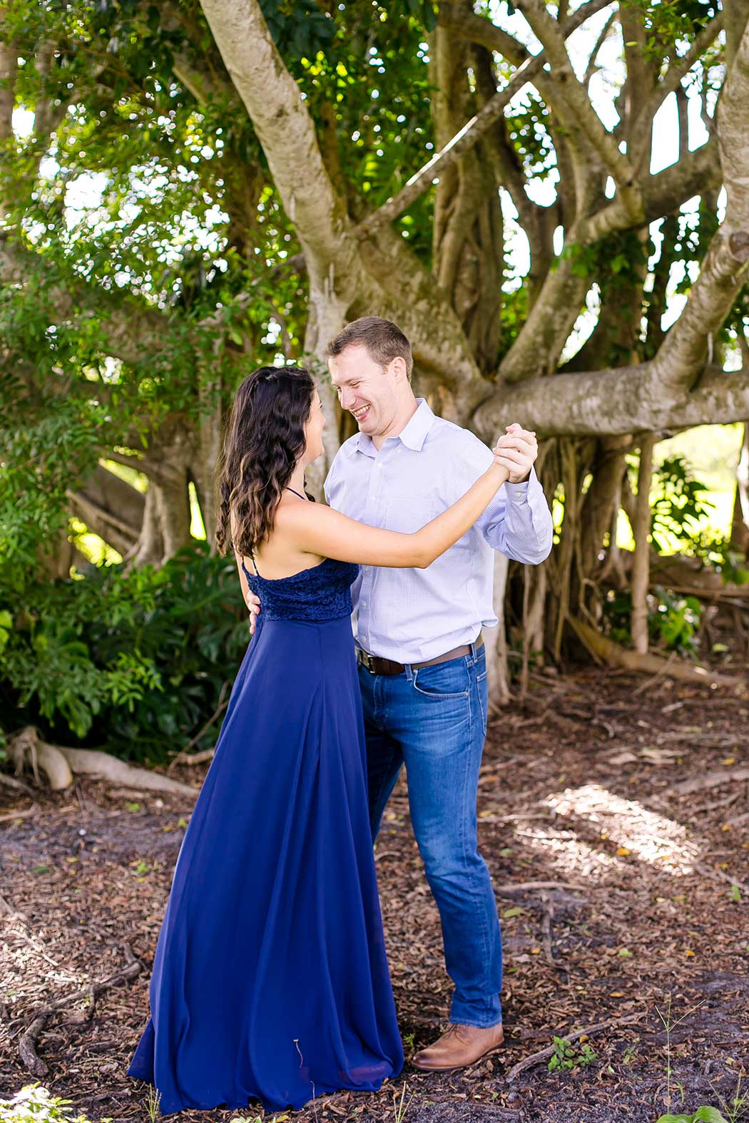 unique photograph of engaged couple dancing in front of large tree | engagement photoshoot fort lauderdale | fort lauderdale engagement photographer