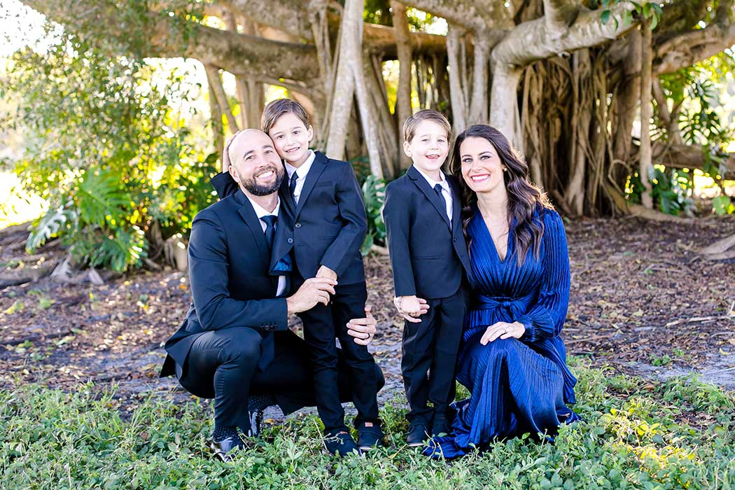 family of 4 taking formal photographs in fort lauderdale park | family dressed up for photographs | beautiful family photographs in robbins preserve | formal family photography fort lauderdale
