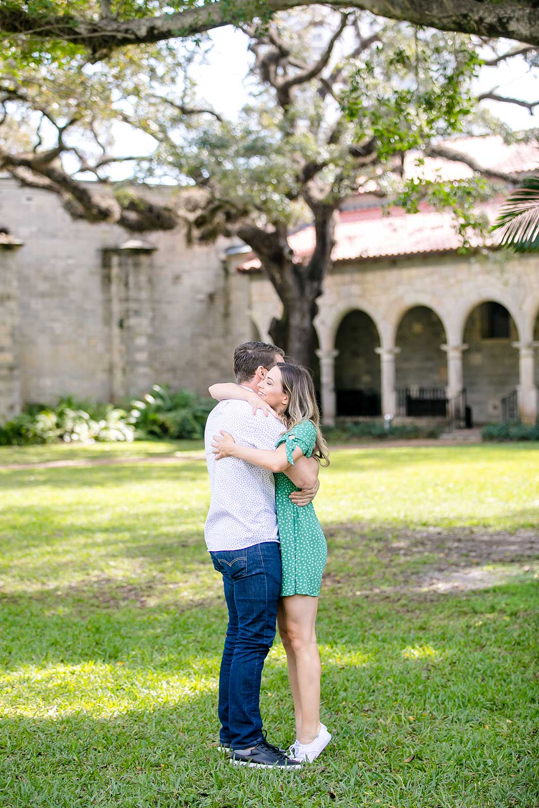 girl hugging boyfriend after surprise proposal | wedding proposal at ancient spanish monastery | engagement photographer fort lauderdale | ancient spanish monastery proposal photographer