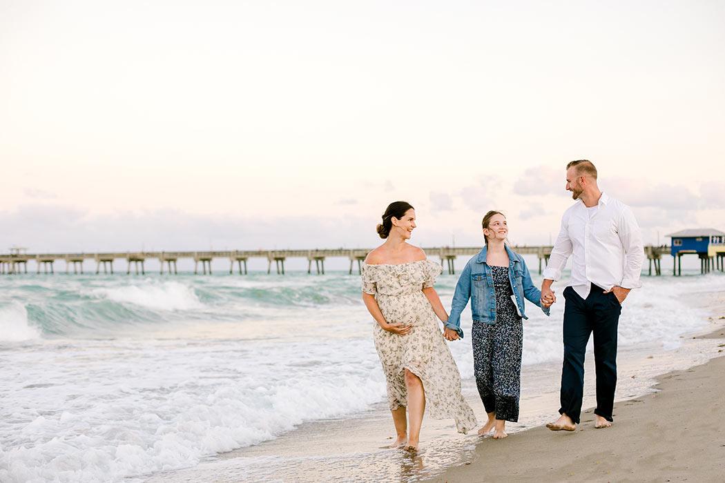beach family maternity photo ideas | family hold hands for maternity photoshoot | walking pose on dania beach with family photographert