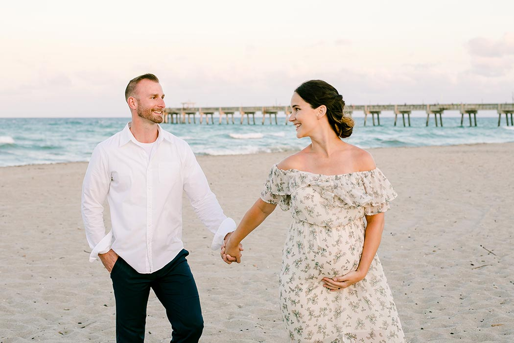 walking beach maternity shot | couple walk on dania beach during maternity photoshoot | dania beach maternity photographer