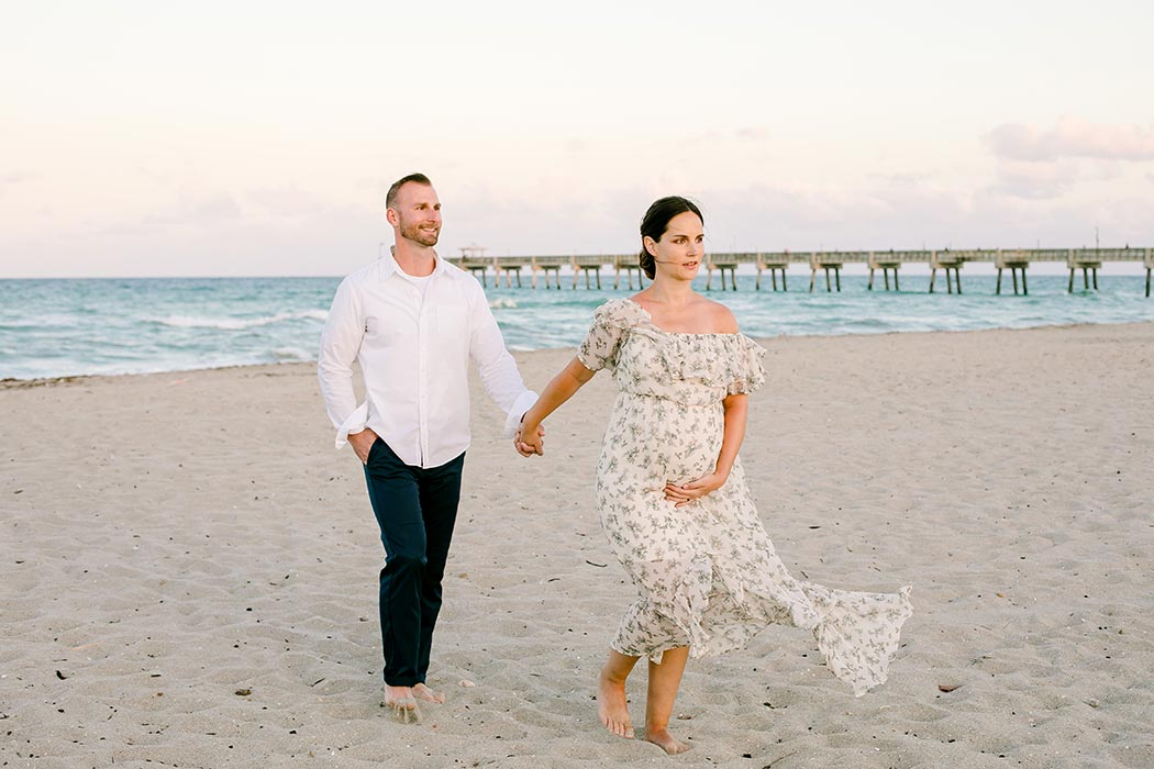 woman and man pose for maternity photography | cute maternity pose | maternity photoshoot on beach | maternity photographer fort lauderdale | dania beach maternity with pier