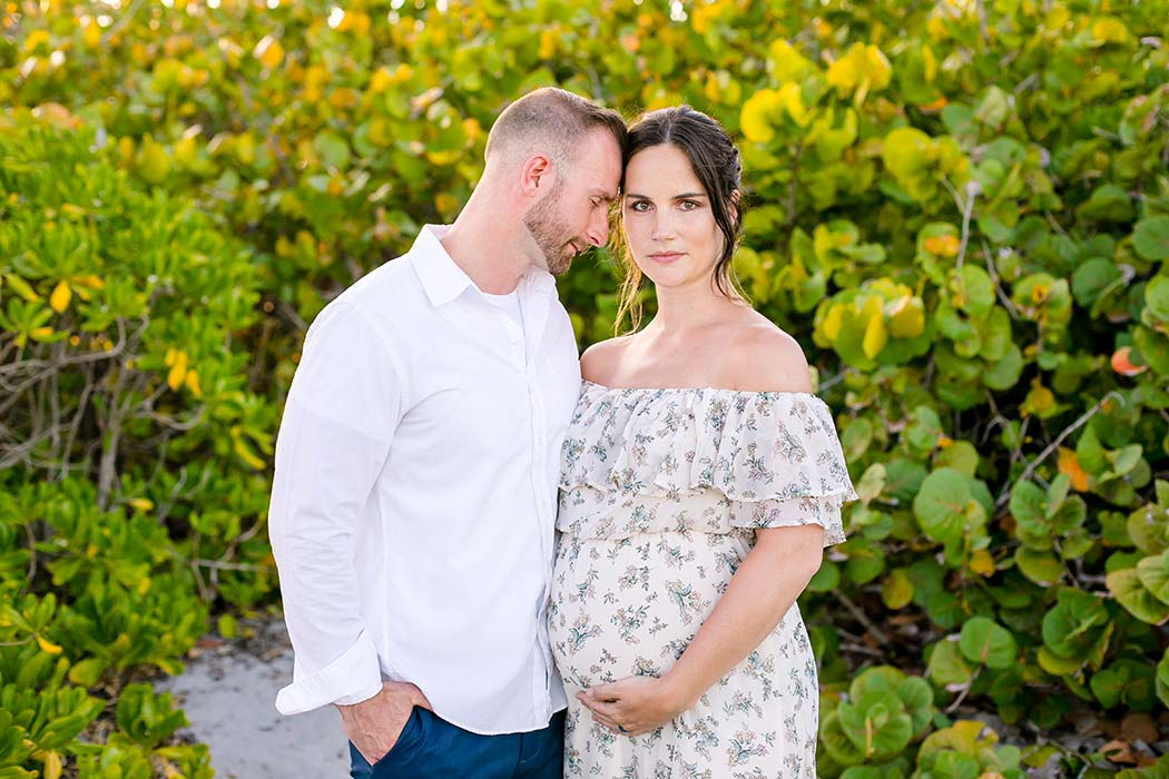 husband and wife pose for maternity photos | expectant mother holds belly in photoshoot | maternity photographer south florida | maternity photography dania beach south florida