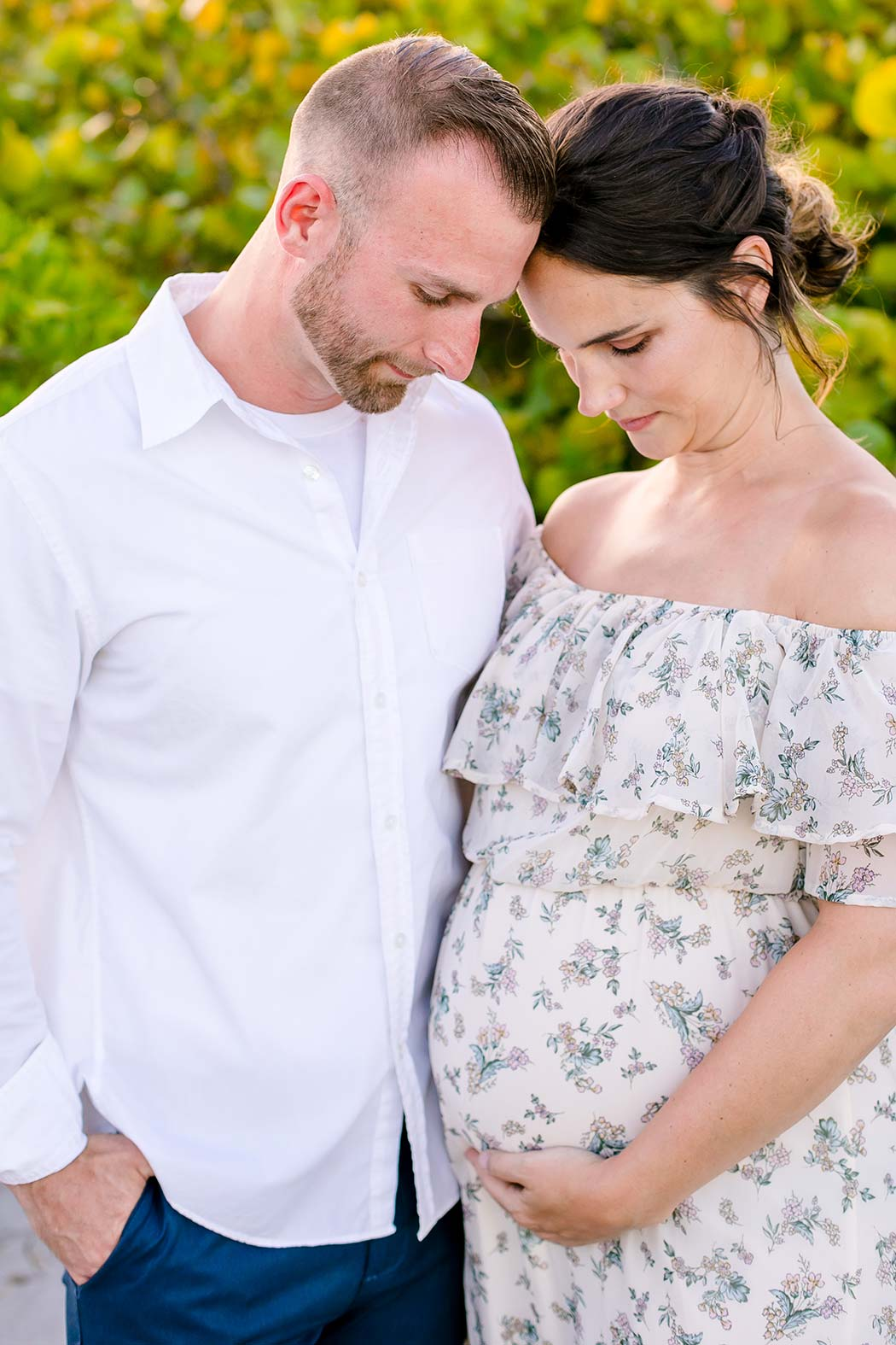 woman holds belly for maternity photography | maternity poses holding belly | floral long maternity dress | maternity session fort lauderdale beach