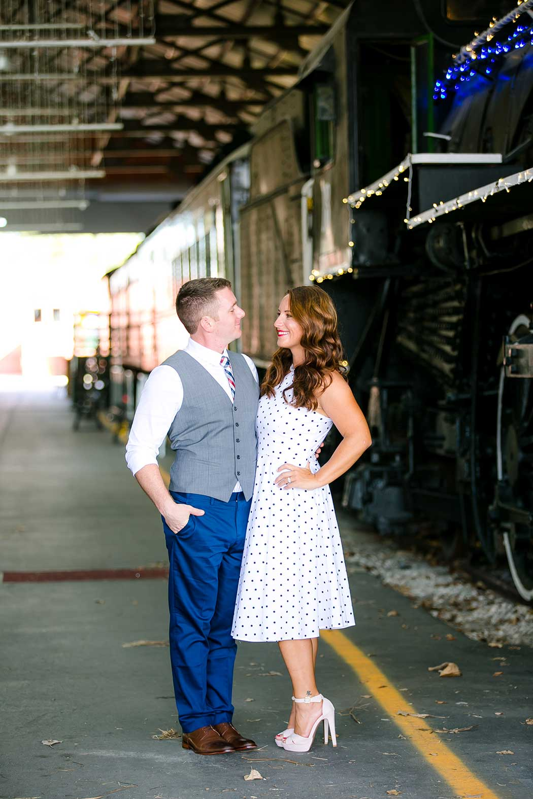 couple pose for engagement photography next to train   gold coast railroad museum photoshoot