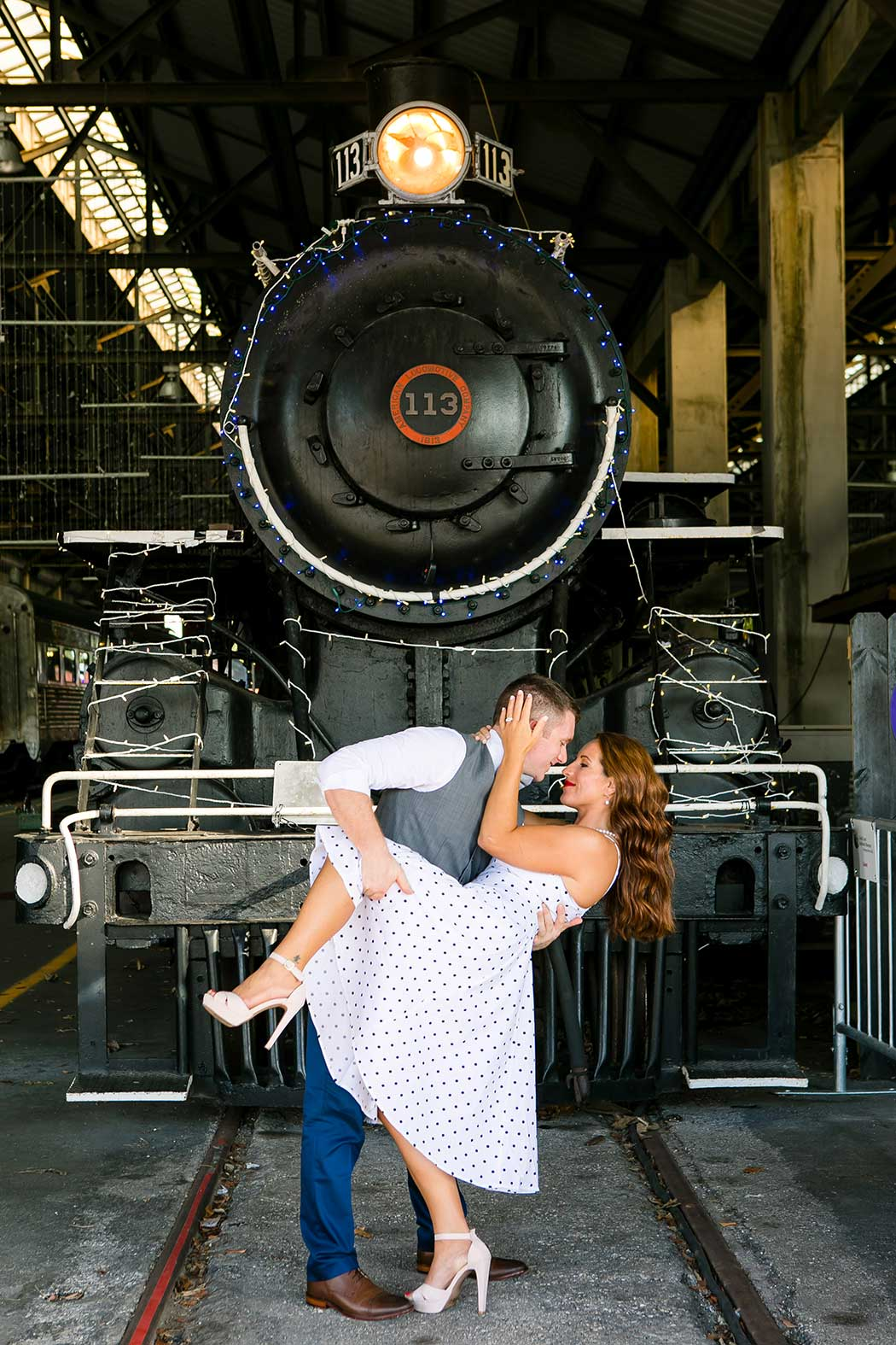 boy dipping girl for engagement photoshoot   boy dips girl picture   engagement session on railroad