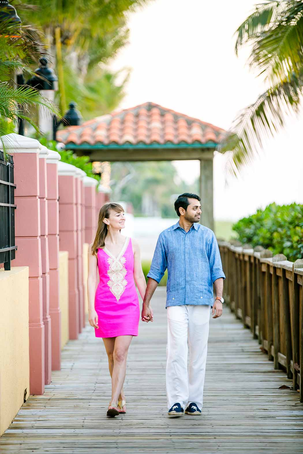 engaged couple walk on wooden walkway | fort lauderdale beach engagement | beach engagement photography fort lauderdale | beach walkway photoshoot in south florida